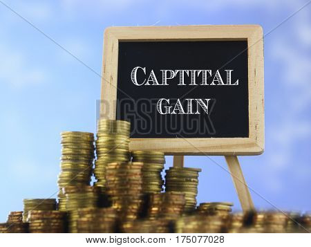 Many piles of coins against  blue sky and mini blackboard with text capital gain