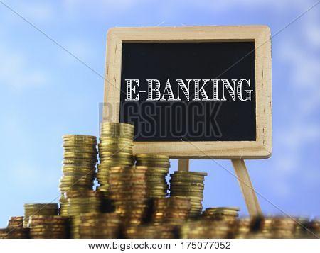 Many piles of coins against  blue sky and mini blackboard with text e-banking