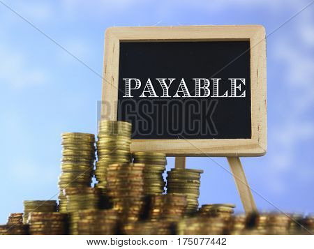 Many piles of coins against  blue sky and mini blackboard with text payable