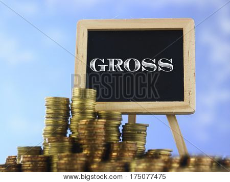 Many piles of coins against  blue sky and mini blackboard with text gross