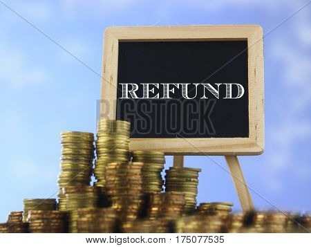 Many piles of coins against  blue sky and mini blackboard with text refund
