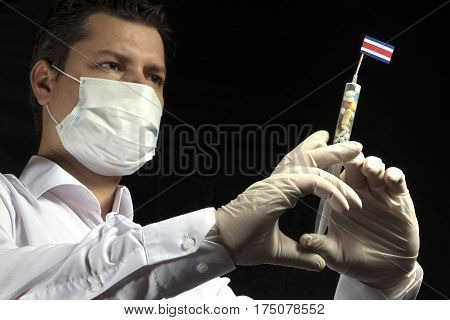 Young Man As A Doctor Gives A Medical Injection To Costa Rican Flag On A Black Background
