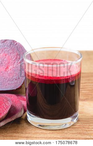 Fresh beet juice in glass and sliced beetroot on wooden table white background