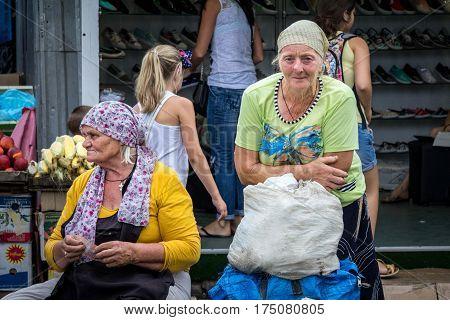 ODESSA UKRAINE - AUGUST 13 2015: Old woman selling vegetables on Privoz market the main market of Odessa Ukraine