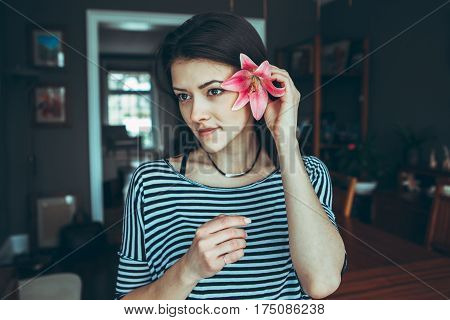 Closeup portrait of smiling pensive Caucasian young beautiful woman model with long hair in striped t-shirt holding large pink flower near ear hair looking away toned with filters