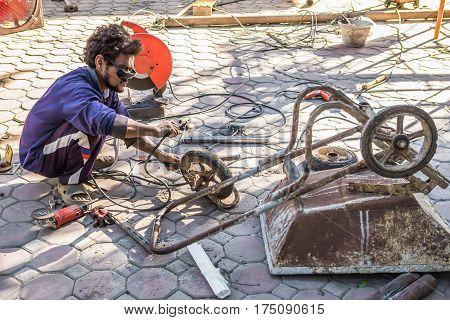 Thailand November 19 2016: Welders repairing cart garbage worn from use.