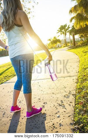 Female jogger in a city park view from behind. Holding a water bottle. View of her legs and body from behind with a sun flare and bright sun shining through