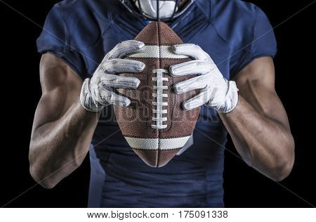 Close up view of an American Football player holding a football. Selective focus on the laces of the football and the wide receiver gloves. Shot on a black background