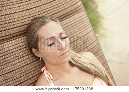 Woman with beautiful eyelashes lounging by the pool outdoors. Gorgeous Woman with beautiful eyelashes lounging outdoors by a swimming pool on a summer day.