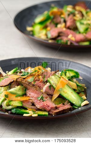 Vertical view of 2 plates of asian beef salad. Inspired by Thai and Vietnamese salads packed with fresh healthy vegetables (carrots onions cucumber etc) and a nicely seared flank steak.