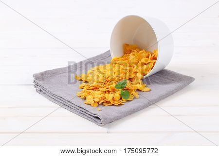 pile of corn flakes spilt out on grey place mat