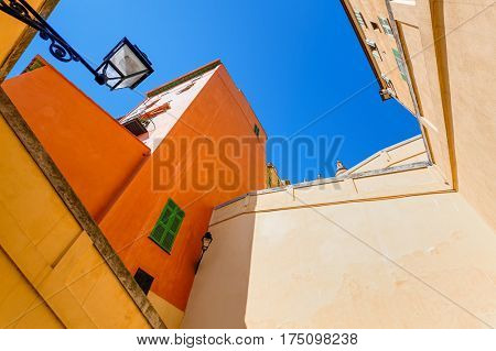 Multicolored walls of old houses under blue sky in Menton, France.