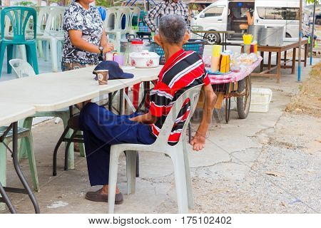 CHIANG RAI THAILAND - MARCH 20 : unidentified old asian leprosy man drinking coffee in paper cup on March 20 2016 in Chiang rai Thailand.