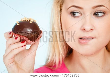 Woman Holding Chocolate Cupcake About To Bite