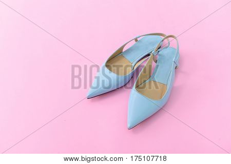 Female light blue shoes on pink background