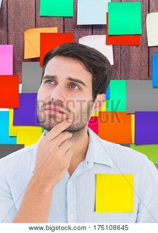 Digital composite image of thoughtful male executive standing against sticky notes