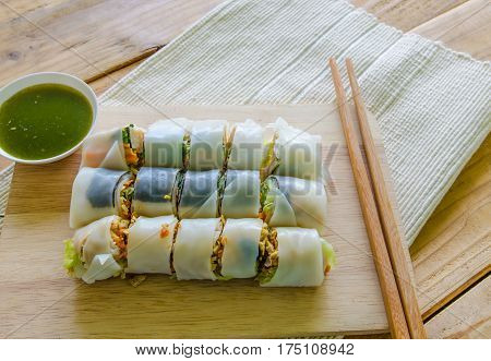 Spring rolls on chopping board with spicy sauce vegetables and in noodle tube.