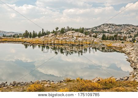 Calm mountain lake with beautiful clouds and reflections and a bit of haze in the distant mountains