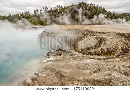 Excelsior Geyser emerging from the steamy mist at Midway Geyser Basin in Yellowstone National Park