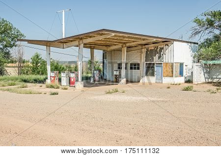 Deserted gas station on Route 66 with windows either broken or boarded up featuring faded and weathered gas pumps