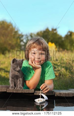 boy and his beloved kitten playing with a boat from pier in a pond summer evening