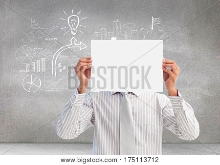 Businessman holding a blank placard in front of his face against grey background with graphics