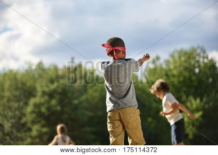 Group of kids plays blind man's buff in summer at the park