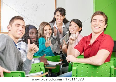 Students and teacher hold their thumbs up in class at school