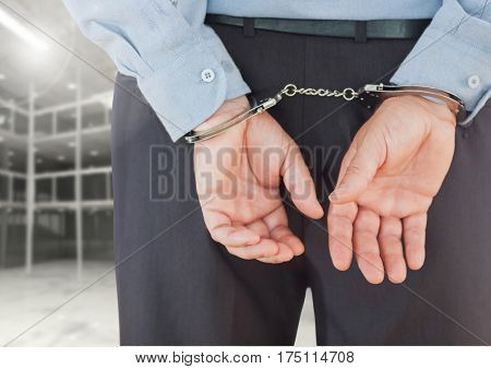 Digitally composite image of corrupt businessman in handcuffs standing against built structure