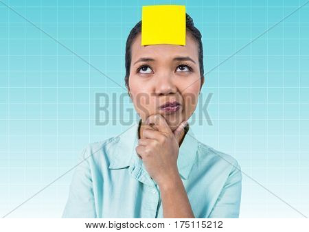 Thoughtful businesswoman with blank yellow sticky note on forehead against blue background