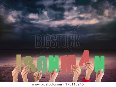 Digitally composite image of hands holding word Ironman against stormy clouds