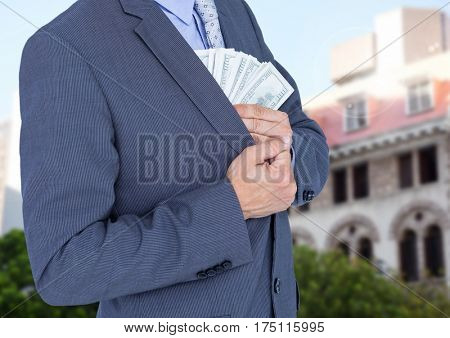 Composite image of businessman hiding money in blazer against house