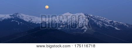 Spring landscape with a full moon over a ridge. Morning twilight with a clear sky. The last snow on the mountain tops. Carpathians, Ukraine, Europe