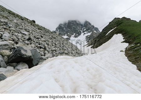 Spring in the mountains. Snow and moraine on the ridge. Cloudy weather. Landscape under the peak Ushba. Zemo Svaneti, Georgia, Caucasus