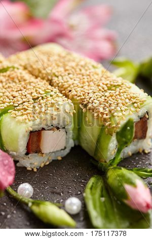 Maki Sushi Roll - Sushi Roll with Cucumber and Sesame outside. Served on Black Stone with Flower. Japanese Cuisine and Natural Flower Concept