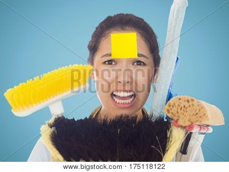 Frustrate woman with sticky notes stick on forehead holding cleaning equipment against blue background