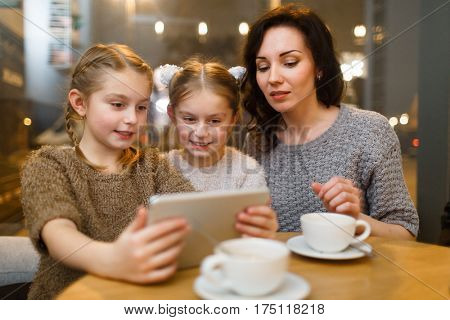 Twins and young woman looking at screen of touchpad by table in cafe