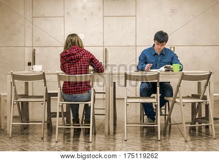 Two Students Man and Woman sitting at wooden Desk inside Campus Chat Room area