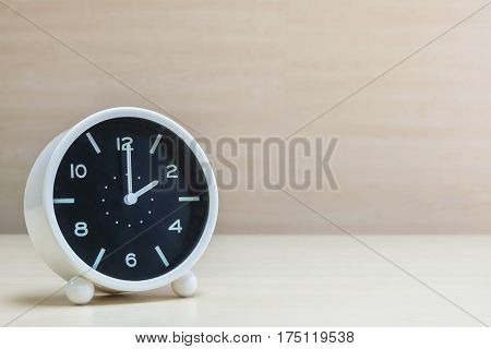 Closeup alarm clock for decorate in 2 o'clock on brown wood desk and wall textured background with copy space