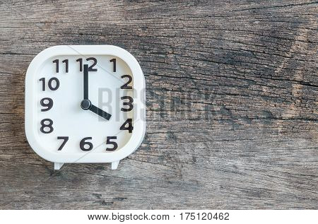 Closeup white clock for decorate in 4 o'clock on old wood floor textured background with copy space