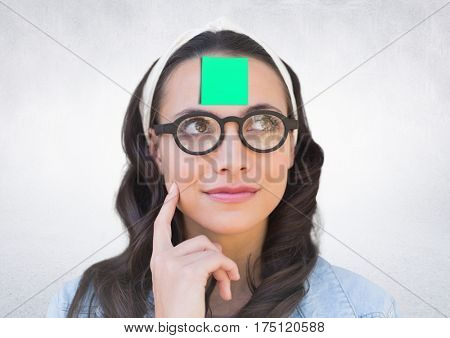 Digital composition of thoughful woman with sticky note stuck on her forehead against white background