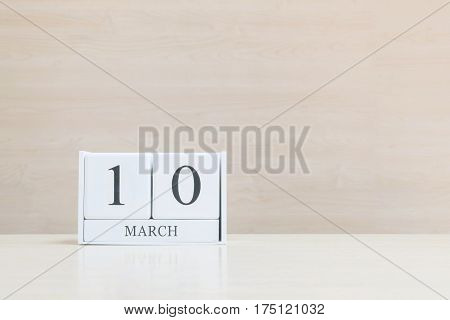 Closeup surface white wooden calendar with black 10 march word on blurred brown wood desk and wood wall textured background with copy space selective focus at the calendar