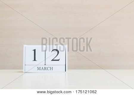 Closeup surface white wooden calendar with black 12 march word on blurred brown wood desk and wood wall textured background with copy space selective focus at the calendar