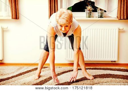 Senior woman doing yoga in living room