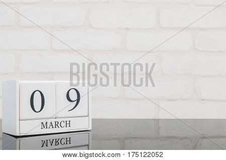 Closeup white wooden calendar with black 9 march word on black glass table and white brick wall textured background with copy space selective focus at the calendar