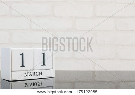 Closeup white wooden calendar with black 11 march word on black glass table and white brick wall textured background with copy space selective focus at the calendar