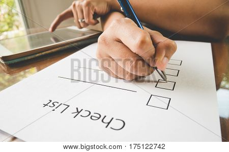 Close- Up Hand Holding Pen On Check List Paper With Tablet In Vintage Style.