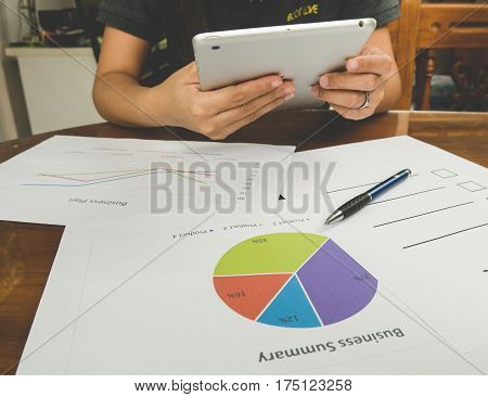 Working Woman Holding Teblet And  Pen On Bussiness Report .