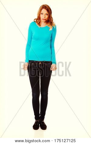 Worried teenage woman showing empty pockets