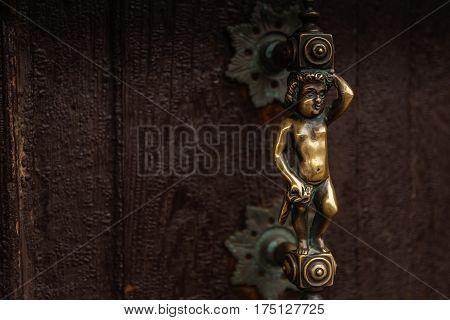 Antique bronze latch on a wooden door in Venice, Italy.